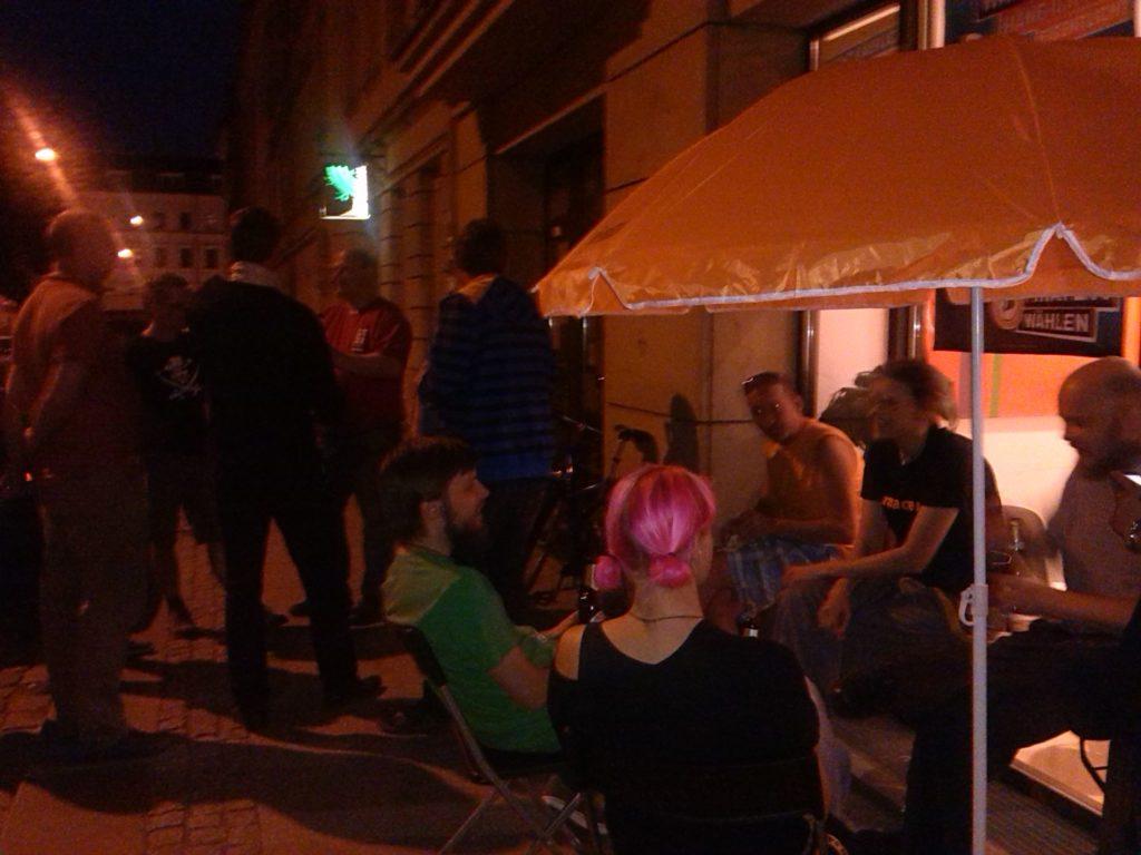 einige Piraten sitzen abends vor der Landesgeschäftsstelle gemütlich beisammen