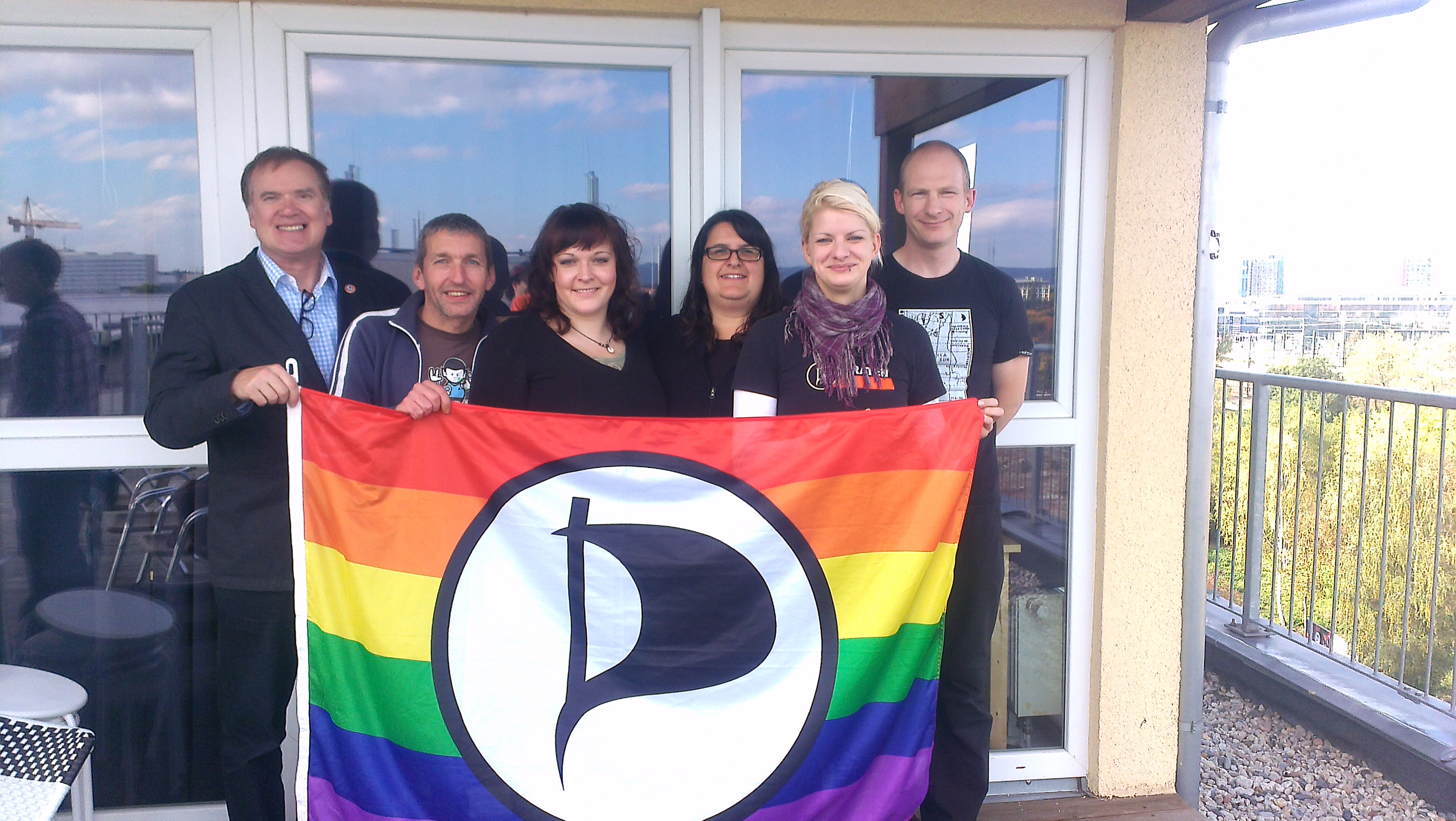der neue Vorstand ist zu sehen mit der Queeratenflagge in der Hand
