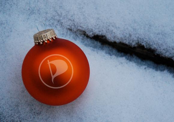 rote Christbaumkugel im Schnee mit Piratensymbol drauf